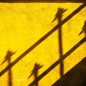 Fence shadow details of four spears on a yellow wall